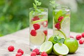 stock photo of tropical food  - fresh cold drink water ice cubes peppermint lime raspberry outdoor summer - JPG