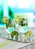 Glasses of cocktail with ice on metal tray on napkin on wooden table on room background