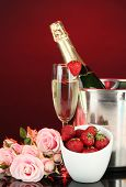 Romantic still life with champagne, strawberry and pink roses, on dark color background