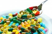 Colorful capsules and pills on plate with spoon, close up