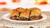 Sweet baklava on plate on table in room