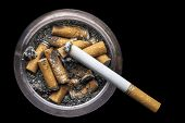 stock photo of butt  - Image of a grungy ashtray with cigarette butts and one lit cigarette on a black background - JPG