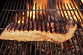 foto of brisket  - Grilled Pork Brisket on Cast Iron Grate in fire background XXXL - JPG