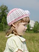 Smiling Little Girl Looks Away At Meadow Near Village At Summer Sunny Day