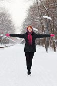 Beautiful Girl In Black Goes With Outstretched Arms Outdoor At Winter Day In Park