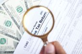 stock photo of irs  - Tax audit concept with a magnifying glasses tax form and money - JPG
