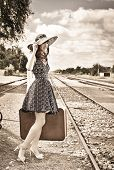 Beautiful woman with  suitcase on a train station. Sepia.