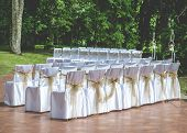 White Wedding Chairs With Brown Bows Outdoors