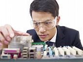 foto of protective eyewear  - young asian man fixing computer with protective eyewear - JPG