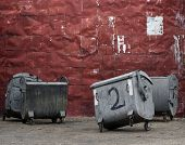 Red Metal Wall With Garbage Containers