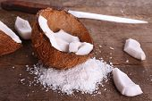 Broken coconut with knife on wooden background
