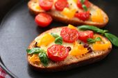 Tasty bruschetta with tomatoes in pan, close up