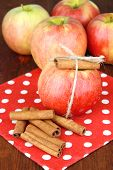 Ripe apples with with cinnamon sticks  on color wooden background
