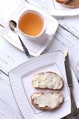 Fresh bread and homemade butter on plate on wooden background