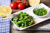 Salad with green beans and corn, and sauce on plate, on color wooden background
