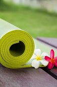 pic of beside  - A yoga mat is set on the floor beside flowers - JPG