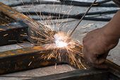 A Worker welding steel with sparks lighting