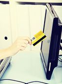 A photo of woman's hand with credit card, in office.