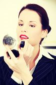 Beautiful business woman is putting lipstick on her lips and holding mirror in office.