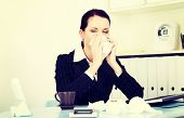Young woman is sneezing. Illness concepion.
