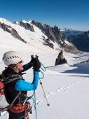 Mountaineer taking picture with a camera in the mountains. Mont Blanc Glacier, Chamonix, France, Eur