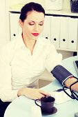 Beautiful business woman is measuring her blood pressure in office.