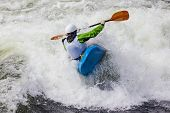 stock photo of kayak  - an active male kayaker rolling and surfing in rough water - JPG