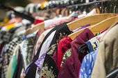foto of down jacket  - clothes on a rack on a flea market.