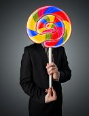 Businessman holding a colorful striped lollipop in front of his head