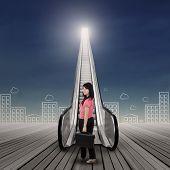Businesswoman Standing On The Escalator