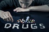 picture of drug addict  - Drugs user preparing drugs to used with razor blade - JPG