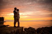 Couple Embracing and Kissing at Sea Sunset