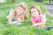 two young happy kids, children reading books on natural background, outdoors