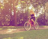 a girl riding a bike on a path in a park full of trees done with
