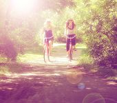two girls riding bikes on a path in a park full of trees done wi
