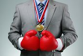 Tough competitive business concept businessman wearing boxing gloves winning first place gold medal
