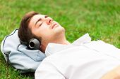Man relaxing on the grass while listening music