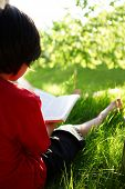 Child reading a book on sunny meadow (with shallow focus and lens flare)