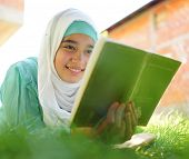 Beautiful Muslim girl reading book with hijab and smiling