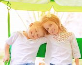 Portrait of two happy kids on swing, enjoying entertainment in summer camp, carefree childhood, acti