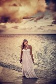 Grunge style photo of beautiful young woman on the beach in overcast weather, dramatic cloudscape, s