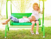 Two adorable child spending leisure time on swing, having fun in summer camp, active holidays, happi