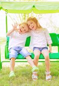 Cute little brother and sister having fun on the swing on backyard, cheerful children in daycare, lo