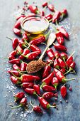 Red Hot Chili Peppers and olive oil over wooden background - cooking or spicy food concept