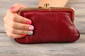 Female hand with stylish colorful nails holding little bag, on wooden background