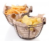 Tasty potato chips and french fries in metal baskets, isolated on white