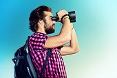 Handsome young man with a backpack looking into the distance with binoculars against blue sky. Activ