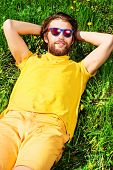Handsome young man lying on a grass and smiles dreamily. Summer rest, vacation.