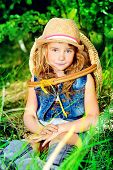 Cute little girl with wicker basket walking through the woods. Summer holiday.