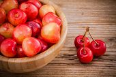 Rainier Cherries In A Bowl On Wooden Background